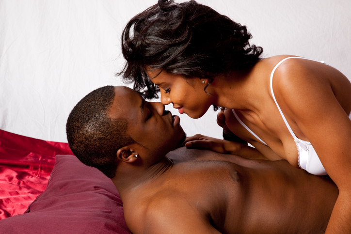 Romantic black couple reclining and kissing in their underwear